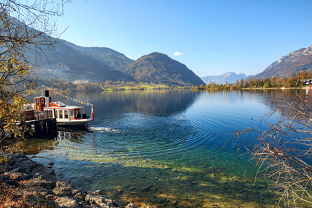 Pleasure boat in the early autumn morning on the lake Grundlsee, moored on the station near village Goessl. Village Goessl, region Salzkammergut, Liezen district of Styria, Austria, Europe.