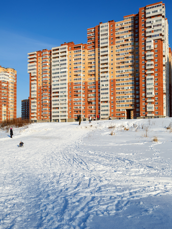 People walking in front of new residential neighborhood, built on the banks of the Pekhorka river. City of Balashikha, Moscow region. Russia.