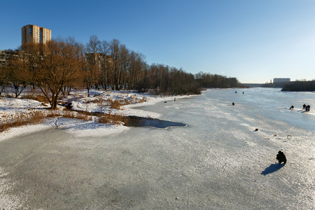 Fishermen fishing on the ice-covered Pekhorka river on a sunny winter day. City of Balashikha, Moscow region, Russia.