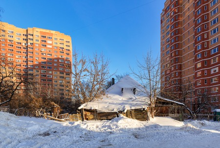 Old dilapidated rickety wooden house in the middle of new residential neghborhood. City of Balashikha, Moscow region, Russia.