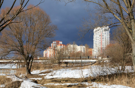 View of the city park, footbridge over Pekhorka river and new residential neighborhood on a stormy spring day. City of Balashikha, Moscow region, Russia.