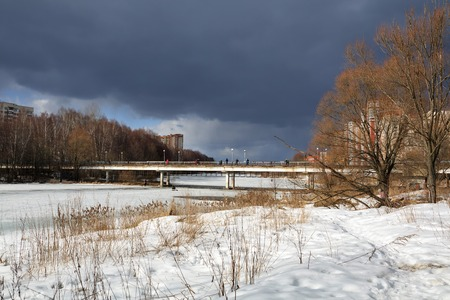 View of the city park and pedestrien bridge over Pekhorka river on a stormy spring day. City of Balashikha, Moscow region, Russia. Stok Fotoğraf