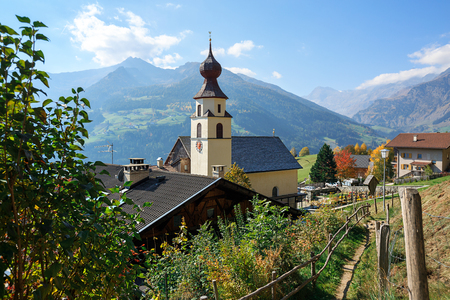 Aerial view of the alpine village of Stulles in province of sunny autumn day. Old parish church. Municipality of Moos in Passeier, South Tyrol, Italy.
