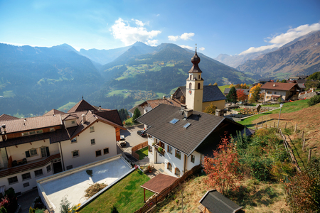 Aerial view of the alpine village of Stulles in province of  sunny autumn day. View of the old parish church. Municipality of Moos in Passeier, South Tyrol, Italy.