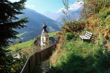 Secluded wooden bench on the mountainside overlooking the alpine village of Stulles. Municipality of Moos in Passeier, Stubai Alps, South Tyrol, Italy. 写真素材