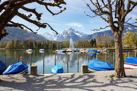 Boats covered with tarpaulin on Walensee lake on a sunny spring day. View of the Alps and lake fountain. Village of Weesen, See-Gaster, canton of St. Gallen, Switzerland.