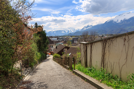 Deserted street leading up the mountain on a sunny spring day. View of the snow-capped Alps. City of Vaduz, Liechtenstein. 写真素材