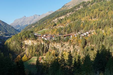 Residential houses located on the mountainside on the river bank, surrounded by forest. Town of Soelden, Imst district, Tyrol, Austria.