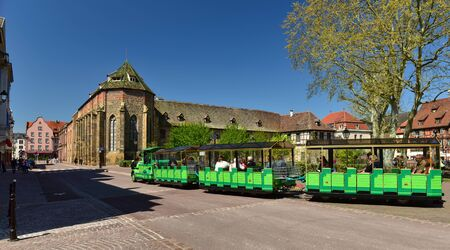 COLMAR, FRANCE - APRIL 18, 2019. Tourist mini train riding in front of the Unterlinden Museum. Town of Colmar, Haut-Rhin, Alsace, France Europe