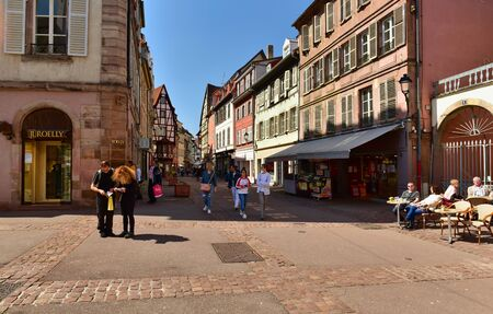 COLMAR, FRANCE - APRIL 18, 2019. People walking along the old street with traditional medieval houses. Rue des Boulangers street, town of Colmar, Alsace, France. Sajtókép
