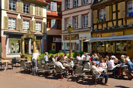 COLMAR, FRANCE - APRIL 18, 2019. People eating in the street restaurant in front of the medieval house in the historical town centre. Place des Dominicains square, town of Colmar, Alsace, France. Editorial