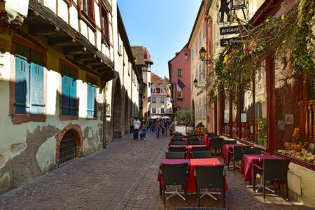 COLMAR, FRANCE - APRIL 18, 2019. Old cobblestoned street in the historical centre. View of the street restaurant. Rue des Marchands street, town of Colmar, Alsace, France.