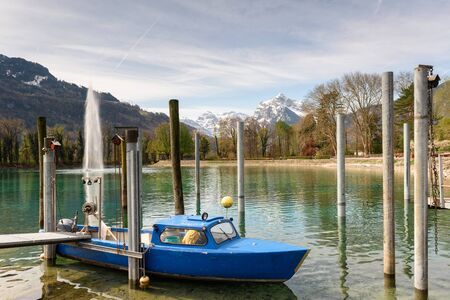 Fishing motor boat moored on Walensee lake on a sunny spring day. View of the Alps and lake fountain. Village of Weesen, See-Gaster, canton of St. Gallen, Switzerland.