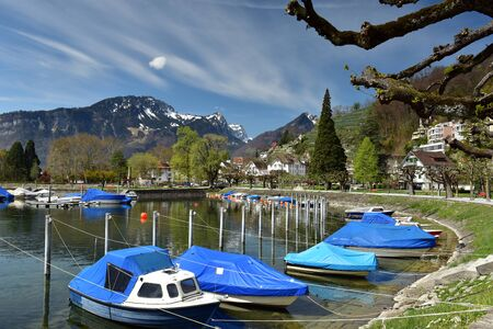 Boats covered with tarpaulin moored on Walensee lake on a sunny spring day. View of the Alps. Village of Weesen, See-Gaster, canton of St. Gallen, Switzerland.