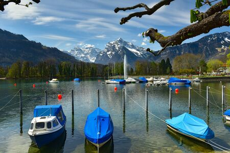 Boats covered with tarpaulin moored on Walensee lake on a sunny spring day. View of the snow-capped Alps. Village of Weesen, See-Gaster, canton of St. Gallen, Switzerland.