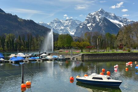 Boats moored on Walensee lake on a sunny spring day. View of the Alps and lake fountain. Village of Weesen, See-Gaster, canton of St. Gallen, Switzerland.