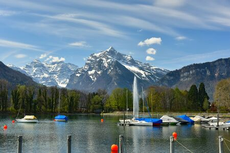 Boats moored on the Walensee lake on a sunny spring day. View of the snow-capped Alps. Village of Weesen, See-Gaster, canton of St. Gallen, Switzerland.