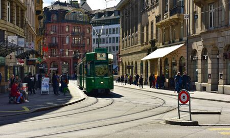 BASEL, SWITZERLAND - APRIL 17, 2019. Green tram driving through the historic center Grossbasel. City of Basel, Switzerland, Europe
