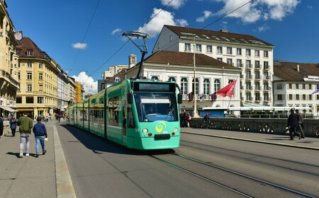 BASEL, SWITZERLAND - APRIL 17, 2019. Green tram on the bridge Mittlere Bruecke. City of Basel, Switzerland, Europe