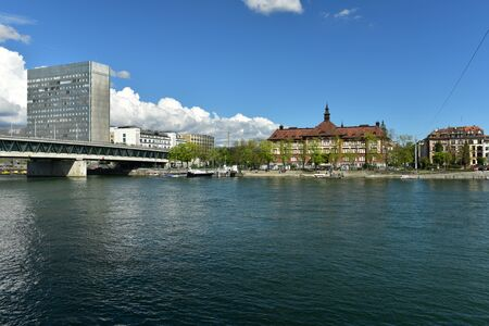 BASEL, SWITZERLAND - APRIL 17, 2019. View of the Rhine river promenade with Dreirosenbruecke Bridge on a sunny day. City of Basel, Switzerland, Europe.
