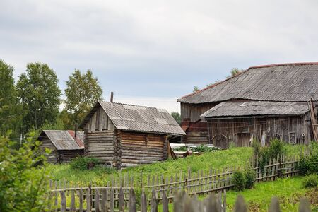 Russian village in summer. Country yard with old log houses surrounded with a rickety wooden fence. Village of Visim, Sverdlovsk region, Russia. Standard-Bild