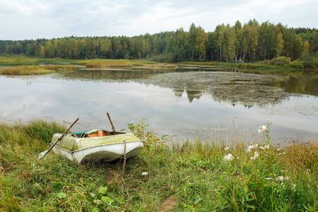 Fishing boat on the river bank on a cloudy autumn day. Russia. 写真素材