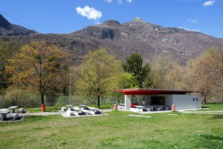 Public Rest area with WC on the highway along the river Reuss near the town of Silenen on a sunny spring day. View of the Alps. Canton of Uri, Switzerland.