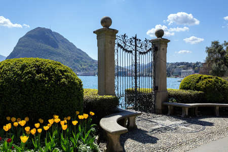 Old gate in Park Ciani at the lake Lugano on a sunny spring day. View of the San Salvatore mountain. Town of Lugano, canton of Ticino, Switzerland, Europe.