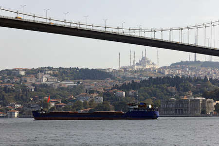 Cargo ship under the Bosphorus Bridge in the Bosphorus Strait. View of the Uskudar district with Camlica Mosque on a hill. City of Istanbul, Turkey.