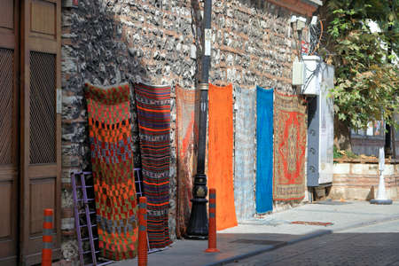 ISTANBUL, TURKEY - OCTOBER 05, 2020. Traditional turkish carpets hanging on the stone wall for sale. City of Istanbul, Turkey. 報道画像