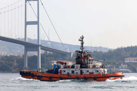 ISTANBUL, TURKEY - OCTOBER 06, 2020. Red ship in front of the Bosphorus Bridge in the Bosphorus Strait. View of the Asian side. City of Istanbul, Turkey.