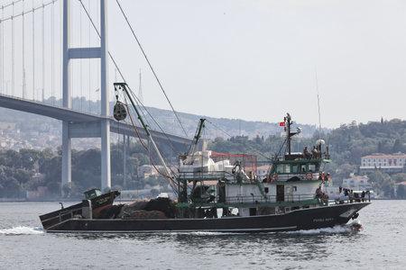 ISTANBUL, TURKEY - OCTOBER 06, 2020. Fishing vessel in front of the Bosphorus Bridge in the Bosphorus Strait. City of Istanbul, Turkey.