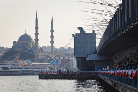 ISTANBUL, TURKEY - OCTOBER 06, 2020. Galata Bridge on the Golden Horn, with the New Valide Sultan Mosque in the background. View of many fishing rods installed on bridge. City of Istanbul, Turkey.