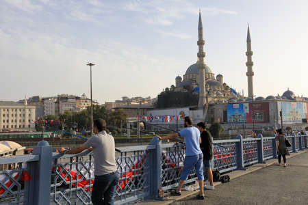 ISTANBUL, TURKEY - OCTOBER 06, 2020. Galata Bridge with the New Valide Sultan Mosque in the background. Fishermen with fishing rods fishing from the bridge. City of Istanbul, Turkey.
