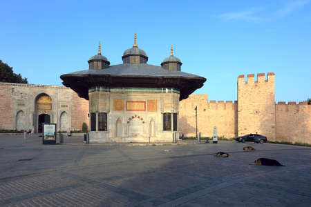 ISTANBUL, TURKEY - OCTOBER 06, 2020. Fountain of Sultan Ahmed III in the great square. View of the Imperial Gate of Topkapi Palace. Sultanahmet neighborhood, city of Istanbul, Turkey.