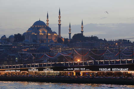 ISTANBUL, TURKEY - OCTOBER 06, 2020. Night view of the Suleymaniye mosque and Galata Bridge, seen from ship during Bosphorus trip. City of Istanbul, Turkey.