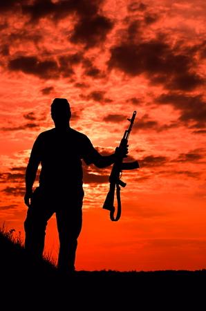 燃えるような空の背景に銃を持つ兵士のシルエット