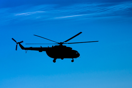 mi: Silhouette of Mi-8 helicopter on blue sky background