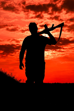 power rangers: silhouette of a soldier with a gun on a background of the fiery sky