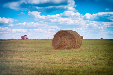 bale of hay on the field, tractor in the distance, retro toning Stock Photo