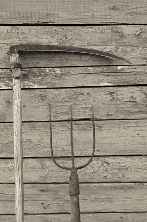 farm implements: pitchfork and scythe on the background of the board, black and white tinting