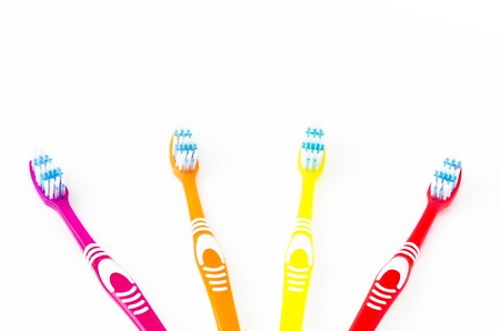 four colored toothbrushes on a white background