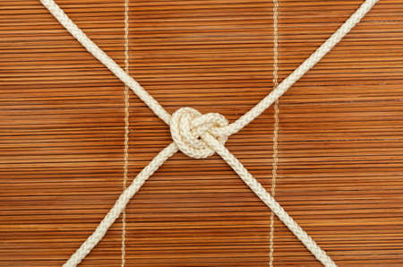 Knot of rope with four ends, on a wooden background