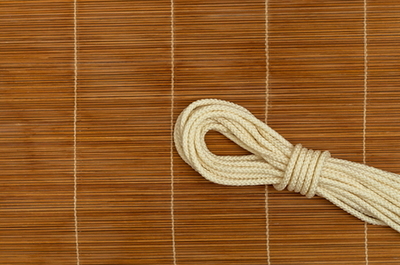 Folded rope, on a wooden background