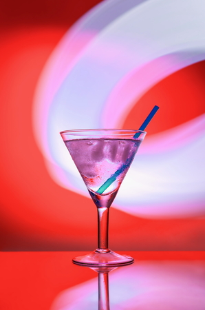 alcoholic drink with ice and a straw in a glass on a red background with lights.