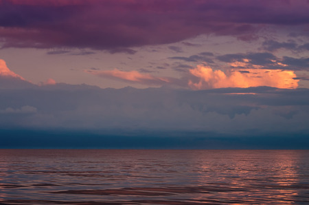 large storm clouds on the Azov Sea, illuminated by the setting sun, the sea horizon. Reflection on the water surface.