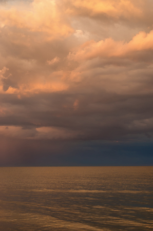 storm clouds on the Azov Sea, illuminated by the setting sun, the sea horizon. vertical composition. Stock Photo