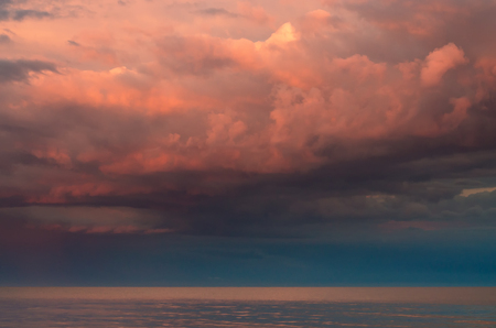 Large thunderclouds of purple on the Azov Sea, lit by the setting sun, the sea horizon. Reflection on the water surface. Stock Photo