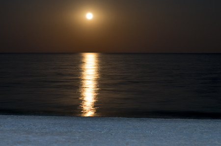 lunar reflection at sea, full moon, beach shore at night