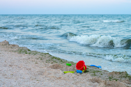 plastic childrens toys on the sea beach, a storm
